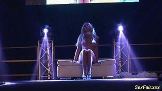 Flexible blonde busty german MILF masturbating on puplic sexfair show stage
