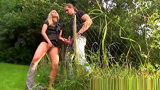 CFNM blonde teen gives blowjob through fence