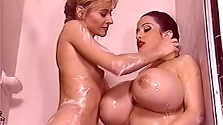Stunning redhead milf with enormous breasts playing with a lean blonde girl