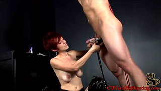 Sizzling dominatrix with short red hair and big tits torturing a stranger