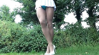 Crossdresser removing skirt to swimsuit outdoors.